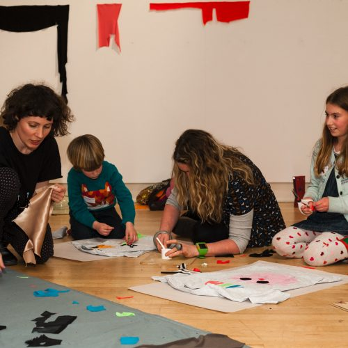 Artist Kate Owens working with three young participants in a creative workshop alongside Generation ART: New Walk Museum and Art Gallery